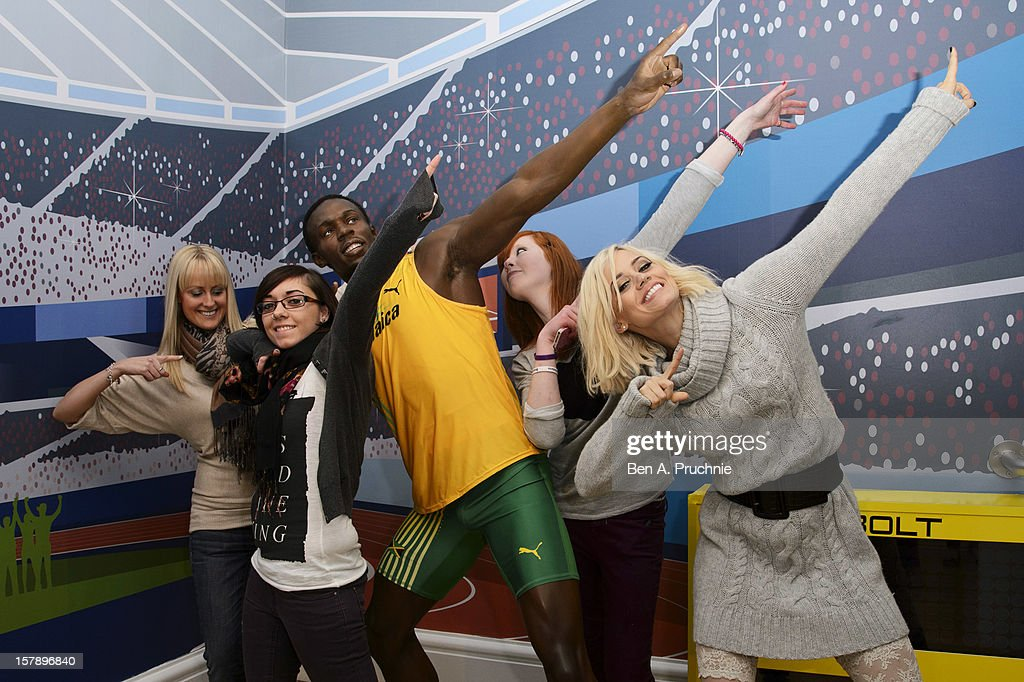 Pussycat Doll Kimberly Wyatt poses with fans next to a wax figure of Usain Bolt at Madame Tussauds on December 7, 2012 in London, England.