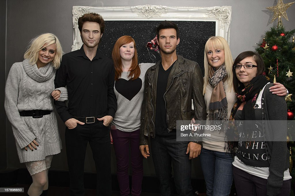 Pussycat Doll Kimberly Wyatt poses with fans next to wax figures of Robert Pattinson and Taylor Lautner at Madame Tussauds on December 7, 2012 in London, England.