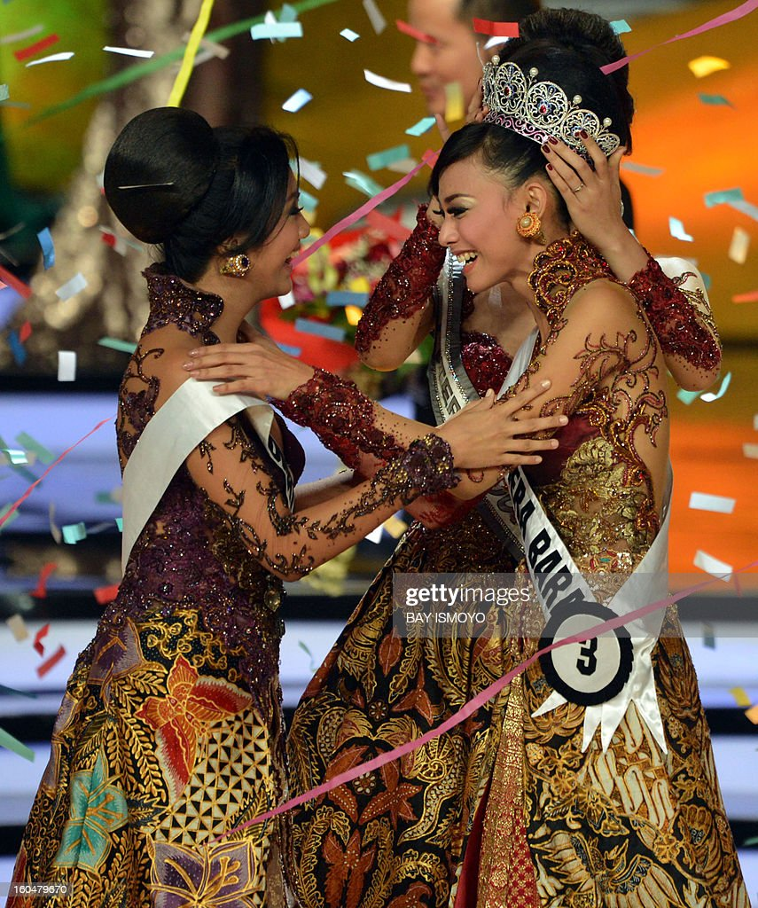 Putri Indonesia 2012-2013 Whulandary (front R) is crowned by Putri 2011 Maria Selena (back R) during the grand final in Jakarta on February 2, 2013 as her competitor Marisa Sartika Maladewi (L) watches. AFP PHOTO / Bay ISMOYO