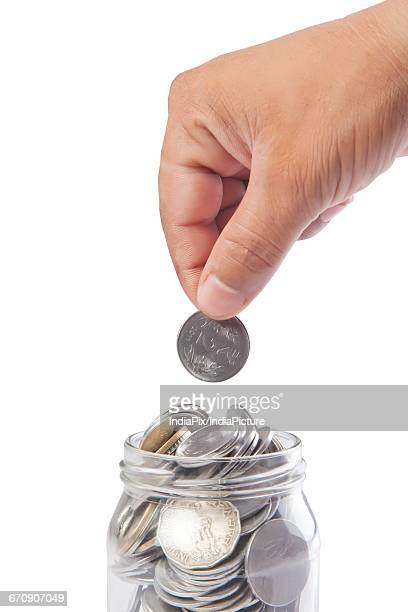 putting a coin into glass bottle, future saving concept