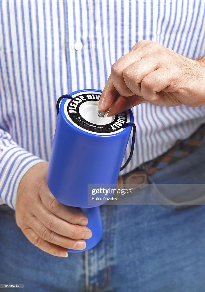 Putting coin into charity donation box