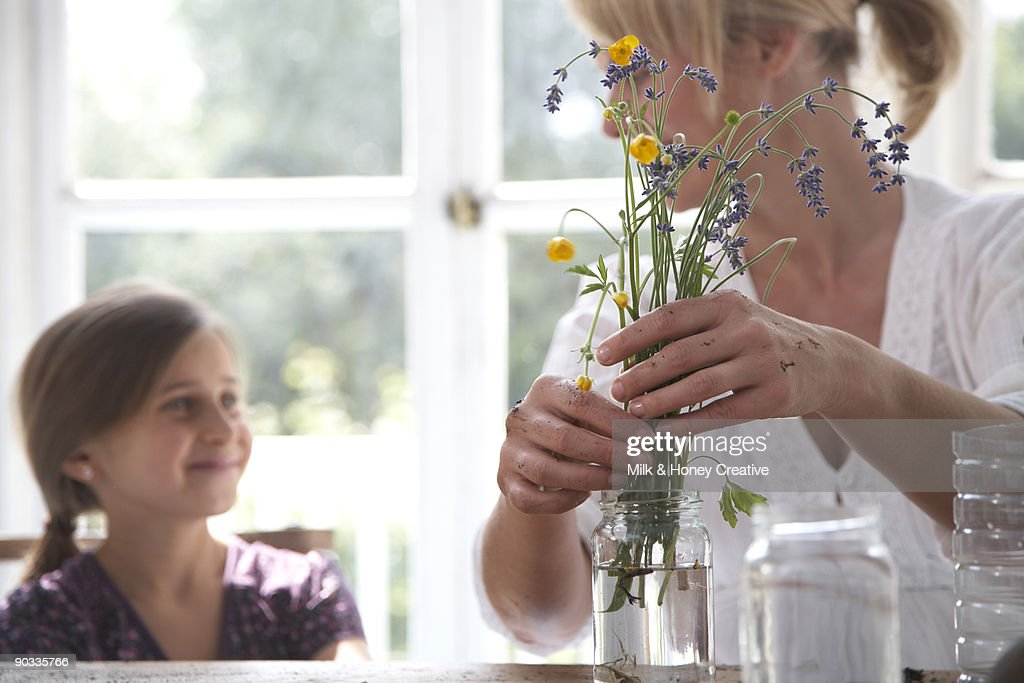 Putting field flowers in recycled pot : Stock Photo