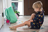 Little girl puts on shoes while anxiously anticipating her first day of kindergarten