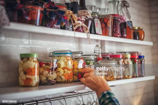 Putting auf dem Regal hausgemachte Gemüse in Gläsern konserviert