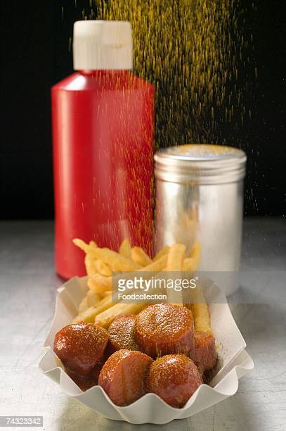 Putting seasoning on sausage with ketchup & chips in paper dish