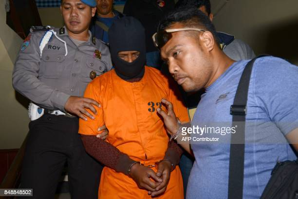 I Putu Astawa a suspect in the murder of an elderly Japanese couple in the Indonesian resort island of Bali is escorted to a press conference at the...