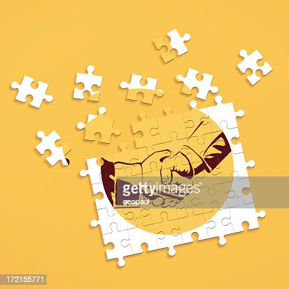 Puzzle pieces forming image of shaking hands
