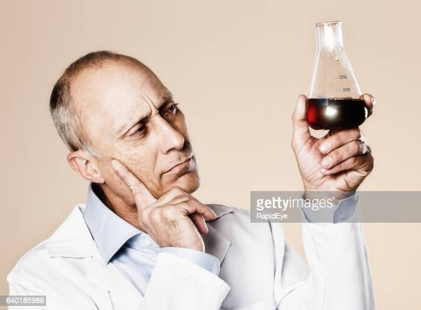 Puzzled scientist frowns, considering dark-red fluid in laboratory flask