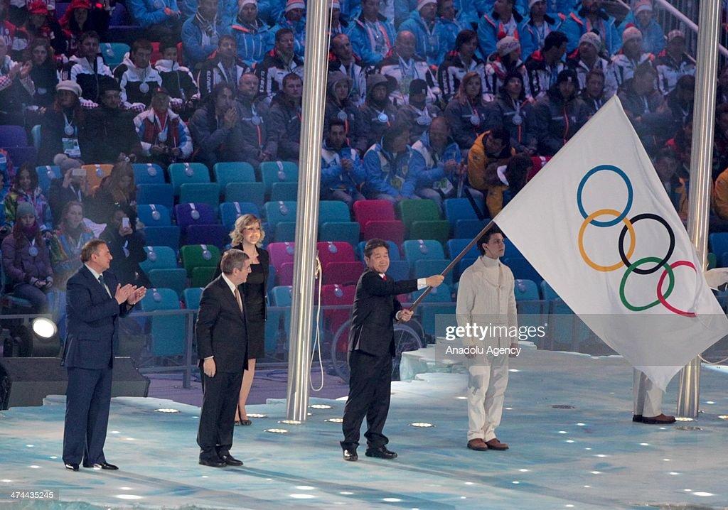 Pyeongchang Mayor Lee Seok-rae (R) waves the olympic flag as IOC president Thomas Bach (C) and Sochi Mayor Anatoliy Nikolayevich Pakhomov (L) look on during the flag handover ceremony at the Closing Ceremony of the Sochi 2014 Winter Olympics at Fisht Olympic Stadium on February 23, 2014.
