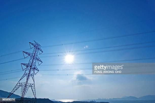 Pylon against blue sky and hazy sun