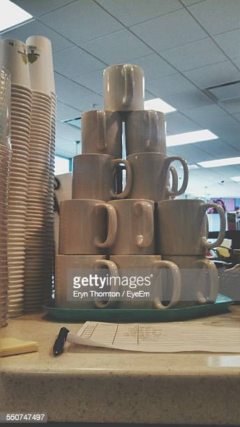 Pyramid Of Coffee Cups Besides Stacked Disposable Glasses In Cafe