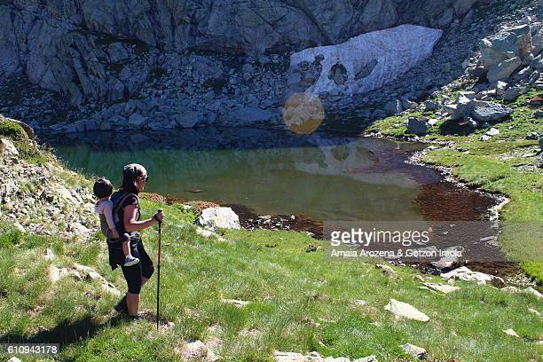 Pyrenees, Huesca province, Spain. Mother hiking and carrying her little daughter in backpack near Bachimaña glacial lake