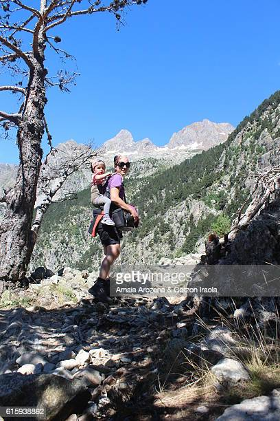 Pyrenees, Huesca province, Spain. Mother hiking and carrying her little daughter in backpack near Panticosa
