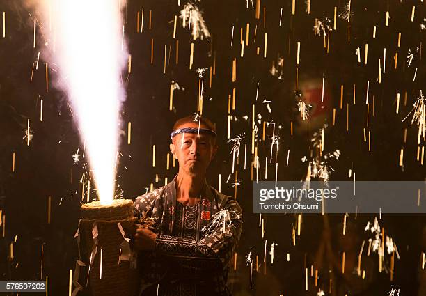 A pyrotechnician holds a bamboo cylinder containing fireworks as he performs 'tezutsu hanabi' or hand held fireworks at the Yoshida Shrine on July 15...