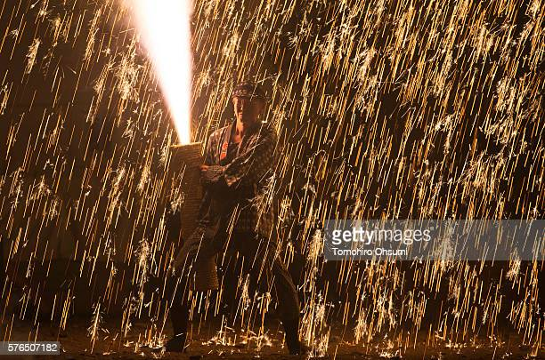 A pyrotechnician holds a bamboo cylinder containing fireworks as they perform 'tezutsu hanabi' or hand held fireworks at the Yoshida Shrine on July...