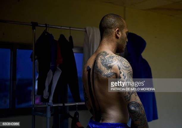 Pysiotape is seen on the back of Brazilian big wave surfer Marcelo Luna as he puts on his wetsuit in preparation for a surf session off Prada do...