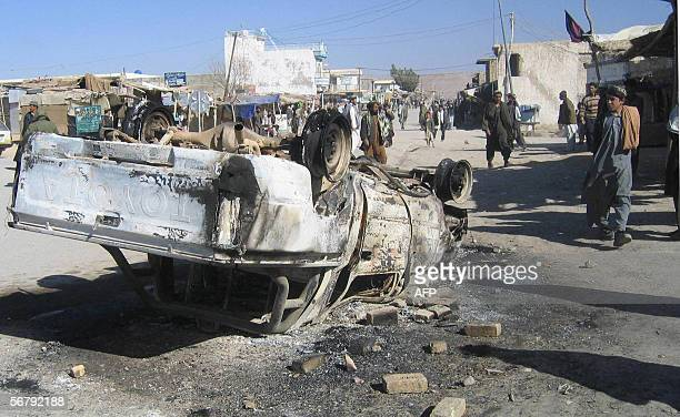 AnAfghan man walks near a police car set alight by protestors offended by the publication of cartoons of Prophet Mohammed in European dailies outside...