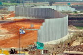 An eightmeter high security barrier aimed at preventing Palestinian suicide bombers from infiltrating Israel separates the newlyopened Cross Israel...