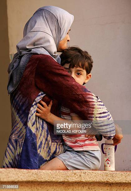 A Lebanese woman hugs her child as they stand on the balcony of their house as United Nations peacekeepers unload food supplies in the southern...