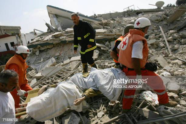 Rescue workers carry dead bodies on a stretcher through the rubble after Israeli air strikes on the southern Lebanese village of Qana 30 July 2006 At...