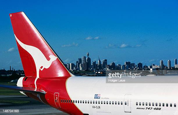 Qantas 747-400 aeroplane tail, Kingsford-Smith Airport, with city skyline beyond.