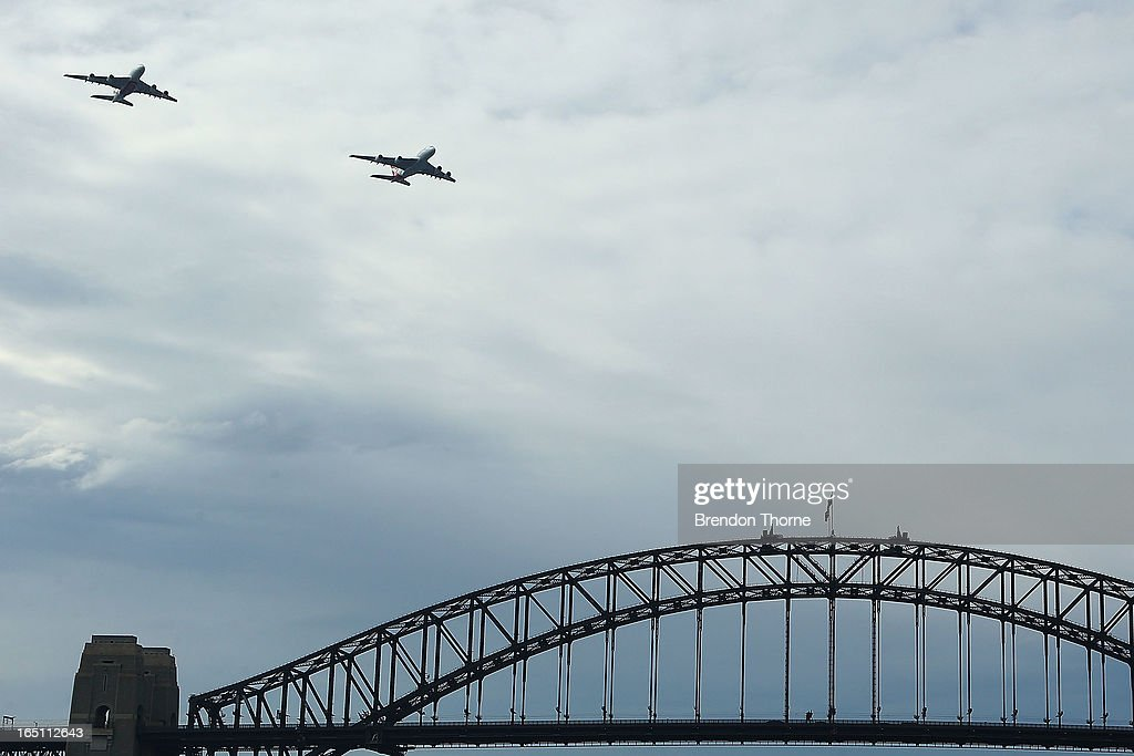 A Qantas Airbus A380 and Emirates Airbus A380 fly over Sydney Harbour on March 31, 2013 in Sydney, Australia. The two Airbus A380s display is believed to be the first of its kind between two seperate airlines to fly over Sydney's Harbour which will mark the alliance between the two airlines.