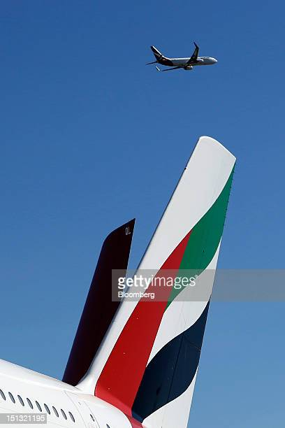A Qantas Airways Ltd aircraft flies past as an Emirates Airline aircraft stands on the tarmac during a media event in Sydney Australia on Thursday...