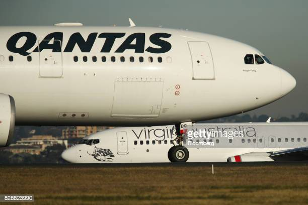 A Qantas Airways Ltd aircraft front and a Virgin Australia Holdings Ltd aircraft taxi at Sydney Airport in Sydney Australia on Thursday Aug 10 2017...