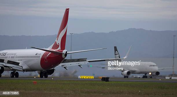 A Qantas Airways Ltd aircraft left and Air New Zealand Ltd aircraft taxi at Auckland International Airport in Auckland New Zealand on Saturday Jan 4...