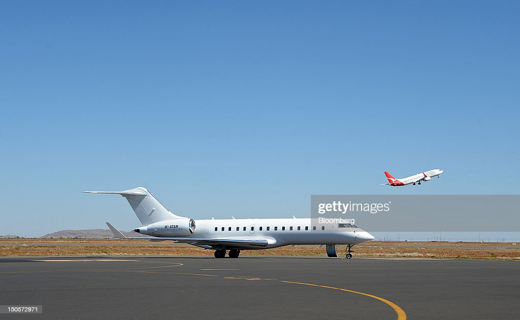 A Qantas Airways Ltd. aircraft, right, takes off as a Bombardier Inc. Global Express jet owned by Australian mining tycoon Clive Palmer stands on the tarmac of Karratha Airport in Karratha, Western Australia, on Monday, Aug. 20, 2012. Palmer expects to receive $500 million a year in royalties from Citic Pacific Ltd.'s $8 billion iron ore mine in Western Australia once it reaches full production. Photographer: Carla Gottgens/Bloomberg via Getty Images