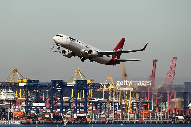 A Qantas Airways Ltd flies in front of gantry cranes as it takes off at Sydney Airport in Sydney Australia on Monday June 22 2015 Australia's central...