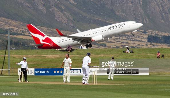 A Qantas jet takes off above the cricketers during day one of the four day warm up International cricket match between New Zealand and England played...