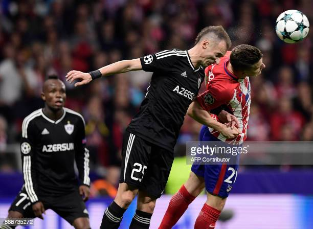 Qarabag's Albanian defender Ansi Agolli vies with Atletico Madrid's French forward Kevin Gameiro during the UEFA Champions League football match Club...