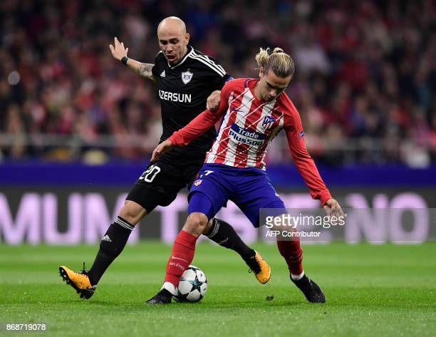 Qarabag's Azerbaijani midfielder Richard Almeida vies with Atletico Madrid's French forward Antoine Griezmann during the UEFA Champions League...