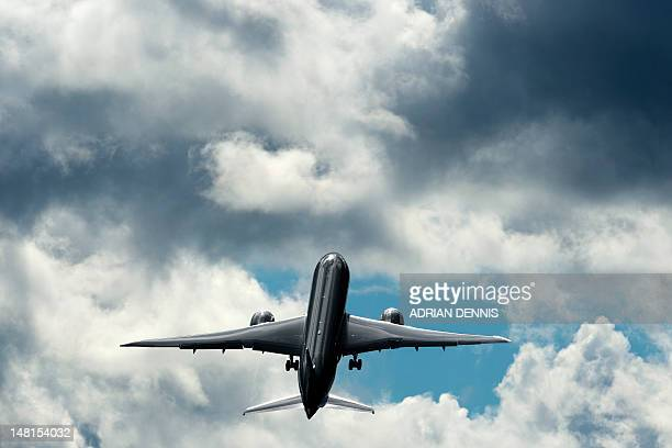 A Qatar Airways Boeing 787 Dreamliner climbs after taking off for a flying display at the third day at the Farnborough International Airshow in...