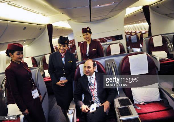Qatar Airways CEO Akbar Al Baker poses with crew members inside a Boeing 777 after the company's press conference at the India Aviation 2010 show at...