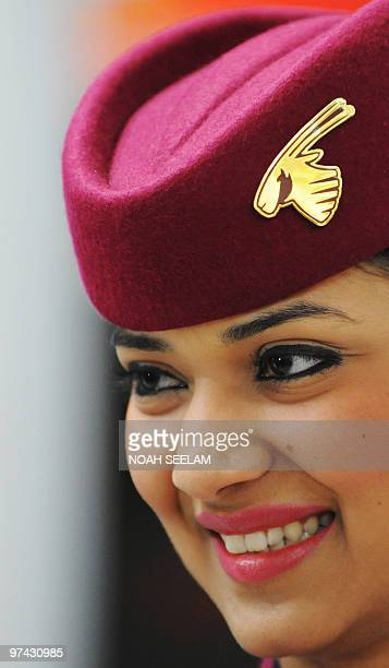 A Qatar Airways crew member welcomes journalists to a Boeing 777 for a photo call with CEO Akbar Al Baker after the company's press conference at the...