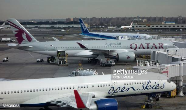A Qatar Airways jet is parked at the terminal on March 21 2017 at John F Kennedy International Airport in New York Passengers traveling to the United...