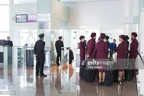 Qatar airways pilots and cabin staff waiting at airport departure gate