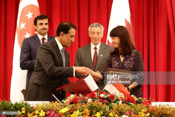 CEO Qatar Investment Authority Abdullah Bin Mohammed Bin Saud Al Thani and Singapore Dean and CEO Civil Service College Ong Toon Hui shake hands...
