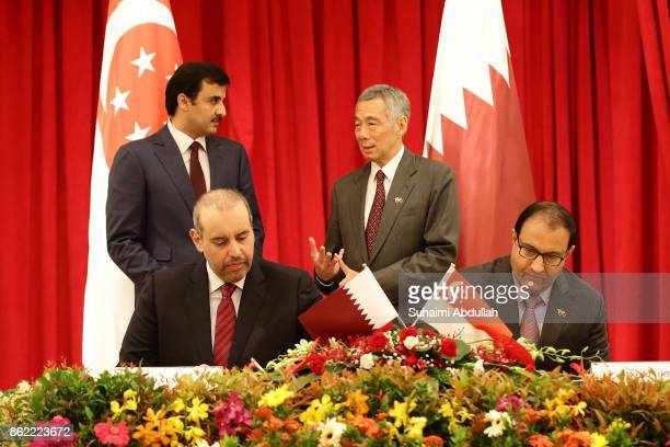 Qatar Minister of Business and Trade Jassim Bin Abdulaziz Bin Jassim Al Thani and Singapore Minister for Trade and Industry S Iswaran sign the...