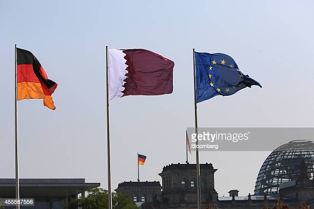 A Qatar national flag center flies between the national flag of Germany left and the European Union flag outside the Chancellery in Berlin Germany on...