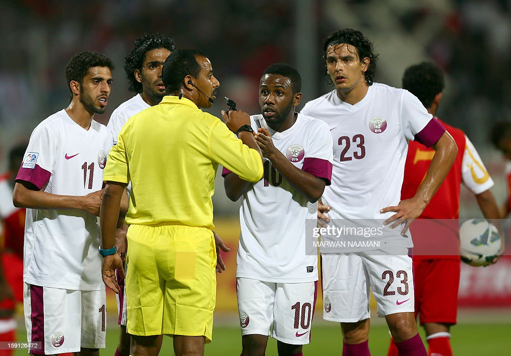 Qatar players argue with the Yemeni referee Mukhtar Saleh after giving Oman a penalty shot against Qatar during the two teams match in the 21st Gulf Cup in Manama, January 8, 2013.