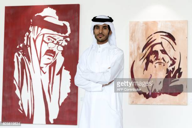 Qatari artist Ahmed Bin Majed AlMaadheed poses for a photo next to some of his paintings at a gallery in Doha on July 28 2017 Maadheed's painting of...