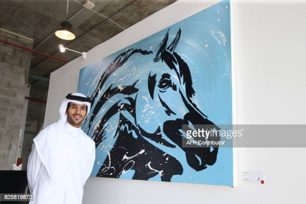 Qatari artist Ahmed Bin Majed AlMaadheed poses for a photo next to one of his paintings at a gallery in Doha on July 28 2017 Maadheed's painting of...