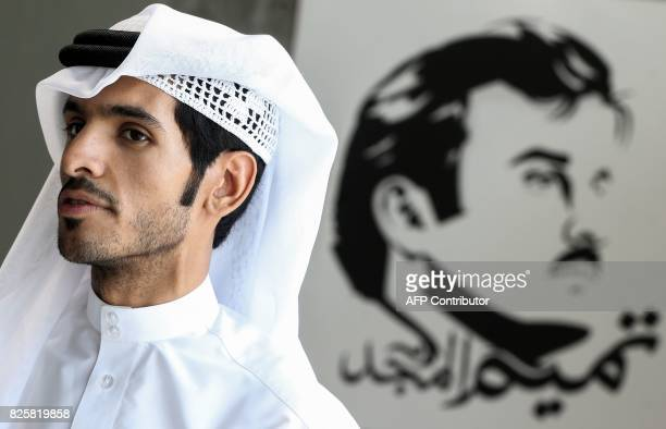 Qatari artist Ahmed Bin Majed AlMaadheed stands next to his painting of Qatari Emir Tamim bin Hamad alThani titled 'Glorious Tamim' at a gallery in...