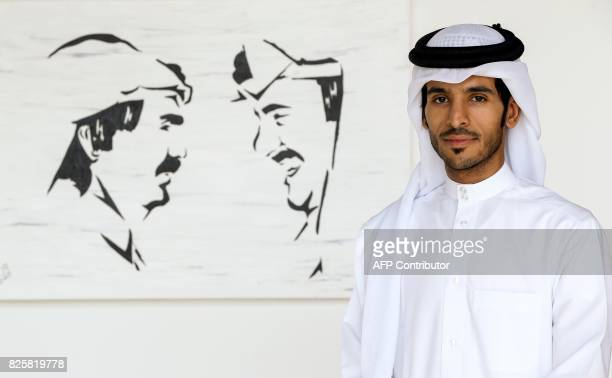 Qatari artist Ahmed Bin Majed AlMaadheed stands next to one of his paintings at a gallery in Doha on July 28 2017 Maadheed's painting of Qatari Emir...