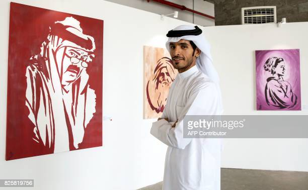 Qatari artist Ahmed Bin Majed AlMaadheed stands next to some of his paintings at a gallery in Doha on July 28 2017 Maadheed's painting of Qatari Emir...