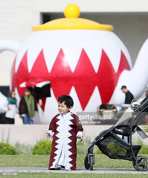 A Qatari child wears an outfit made with the Qatari national flag pattern during celebrations marking the Gulf emirate's national day in Doha on...