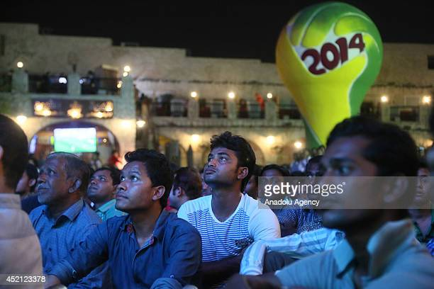 Qatari citizens watch a live broadcast of World Cup final soccer match between Germany and Argentina at the historical shopping centre in capital...